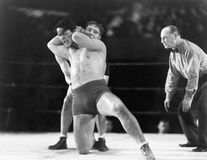 Two men wrestling with referee making a call in the background Stock Images