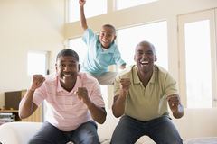 Two men and young boy in living room cheering Stock Images