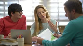 Two men and a young woman discussing a business project in the office. Young business team at work. Two men and a young woman discussing a business project in stock footage