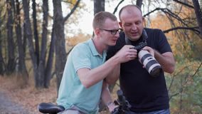 Two mens looks pictures on the big camera screen, speaking and smiling. Forest background. stock video
