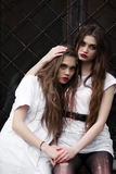 Two mentally sick sisters in strange dark hospital. Picture of two beautiful scared frightened girls in white clothes on black bac Stock Images