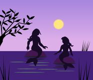 Two Mermaids. Sitting and talking in the moonlight Stock Images