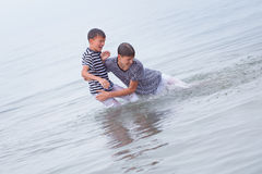 Two merry, happy, brother plays at sea Stock Photo