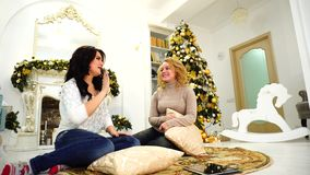 Two merry sisters together spend time and socialize, sit on floor in background of fireplace and Christmas tree in large. Funny girls chat and joke, smile at stock footage