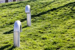 A couple of metal snorkel pipes of a subway meet at a public park on  green grass. stock images