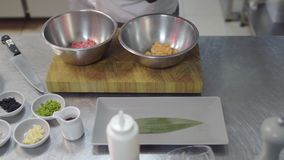 Two metal bowls in the cutting board with cutted salmon and tuna fish. Hands in black latex gloves prepare food. Two metal bowls in the cutting board with stock footage