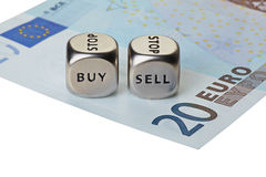 Two metal dices with words Buy and Sell on twenty-euro banknote Royalty Free Stock Image