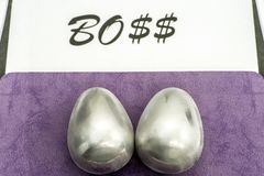 Two metal eggs on the office desk opposite the word Boss. The concept of power.  royalty free stock photos