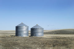 Two Metal Grain Bins. On the praire, with a bright sun Royalty Free Stock Photo