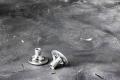 Two metal grey fasteners for gluing on left part of oblong shot on background of black chalkboard rustic surface. Horizontal with. Copy space for design stock images