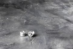 Two metal grey river nuts and clinch bolts on left part of oblong horizontal shot on background of black chalkboard rustic surface. With copy space for design stock photography