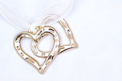 Two metal hearts on light background Royalty Free Stock Image