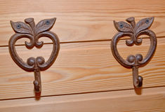 Two metal hooks hangers in the form of apples on a wooden wall Stock Images