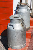 Two metal milk churns on wooden stairs Royalty Free Stock Photo