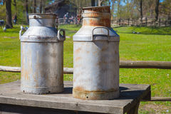 Two metal milk churns on wooden table Stock Photo