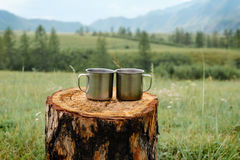 Two metal mugs on a wooden stump. Two metal mugs on a wooden stump on a background of mountains Royalty Free Stock Image