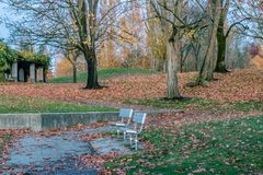 Park with benches in fall. Two metal park benches by the side of a path in an autumn park near an overgrown structure Stock Image