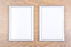 Two metal photo frames on the table. Two metal photo frames on wooden table Stock Image