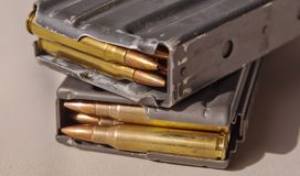 Two metal rifle magazines, one stacked upon the other royalty free stock photo