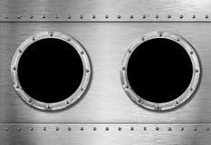 Two metal ship portholes stock photography