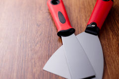 Two metal spatula with a red handle on wooden background Royalty Free Stock Image