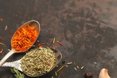 Herbs and spices on dark old table. Two metal spoons with rosemary and saffron on dark old table or background with copyspace for menu. Dark moody photo Stock Image