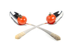 Two metal spoons with tomatos Royalty Free Stock Photos