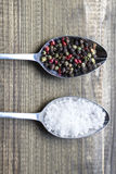 Two metal spoons witlh salt crystals and color peppercorns on wooden table. Royalty Free Stock Photography
