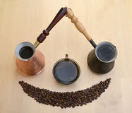 Two metal Turks, a cup about coffee and coffee grains on a light Stock Image