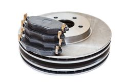 Two metallic brake disks and pads isolated on white background. Two metallic brake disks and pads isolated on white Stock Images
