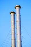 Two metallic tubes, blue sky background. Royalty Free Stock Photos