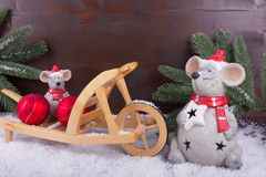 Two mice with christmas balls on wooden wheelbarrow Stock Photos