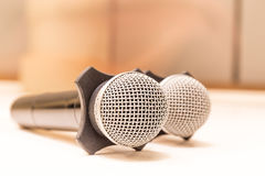 Two microphones with warm fall color and blurred focus meeting r Royalty Free Stock Photography