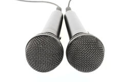 Two microphones on a white background- var. 1. The photo can serve as an illustration to ideas of communication, dialogues Stock Image