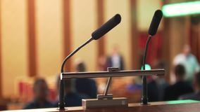 Two mics on stage in front of empty auditorium - business conference. Close up stock footage