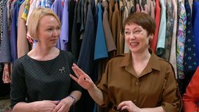 Two middle age women designers talk about fashion trends on the background of clothing. Two middle age women designers talk about fashion trends in clothing stock video footage