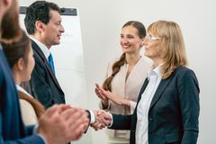 Two middle-aged business associates smiling while shaking hands. As agreement after meeting in the conference room of a multinational company Royalty Free Stock Photography