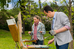 Two middle-aged dreamy artists during an art class in a garden. Two middle-aged dreamy artists working  on a trestle and easel painting with oils and acrylics Stock Image