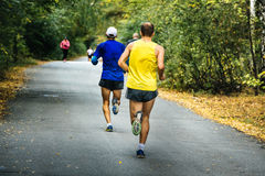 Two middle-aged men running in autumn Park stock photos