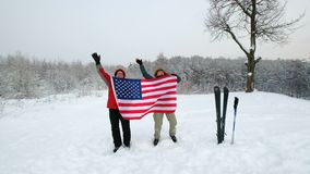 Two middle-aged men sport fans waving an American flag. In the winter ski slope background stock footage