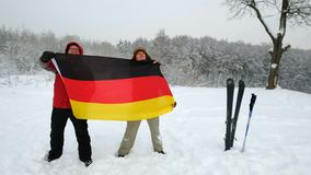 Two middle-aged men sport fans waving Germany flag. Two middle-aged men sport fans holding waving Germany flag in the winter ski slope background stock video footage