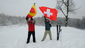 Two middle-aged men sport fans waving Germany flag. Two middle-aged men sport fans holding waving Germany and Switzerland flags in the winter ski slope stock footage