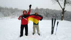 Two middle-aged men sport fans waving Germany flag. In the winter ski slope background stock video footage