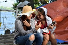 Two 2 middle aged women having fun sharing thoughts and stories holding smart phone. stock photos