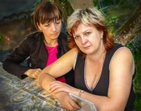 Two middle-aged women resting in the Park. Two middle-aged women relax in the Park sitting at the table royalty free stock photography