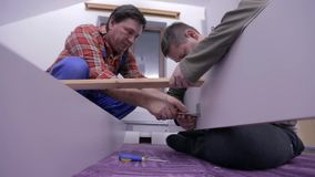 Two middleaged men assemble the furniture in white room for the first time. Two men are assembling new furniture in freshly painted room. They use compact stock video footage