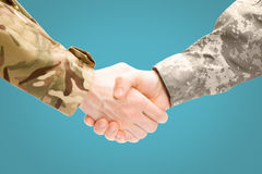 Two military men shaking hands on white background - close up studio shot on light blue background Royalty Free Stock Photo