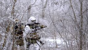 Two military men in white camouflage and green uniform, in winter forest. Soldiers with machinegun join and sneaking front view.