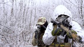 Two military men in white camouflage and green uniform, in winter forest. Soldiers with machinegun sneaking up alonge road, front