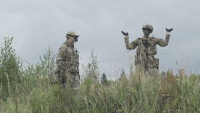 Two military standing in the field, one of them dancing on the hill stock video footage